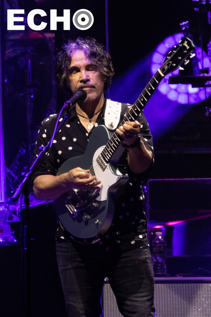 John Oates is feeling the music as he plays guitar with his eyes closed.