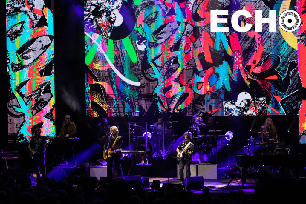 Hall, Oates, and the band play in front of colorful backdrop
