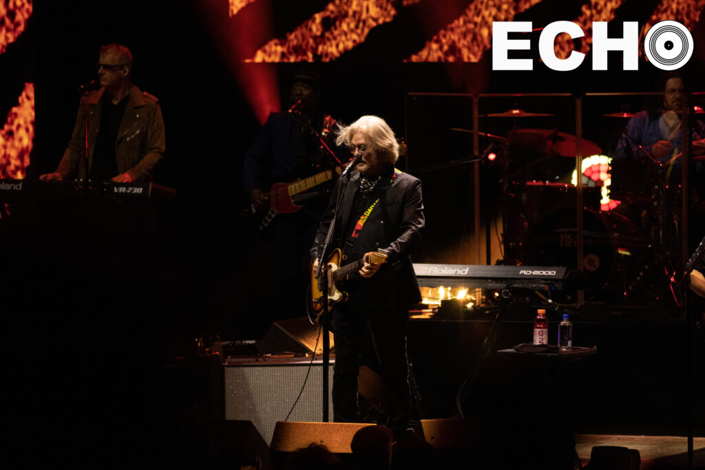 Daryl Hall plays guitar and sings at microphone